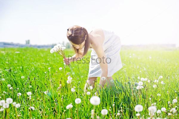 Девушка на поле с одуванчиком