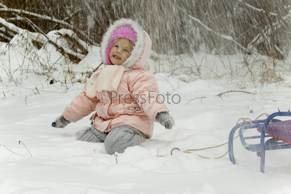 Snow falls on the girl