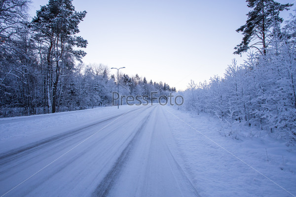 Winter evening forest with road covered with snow