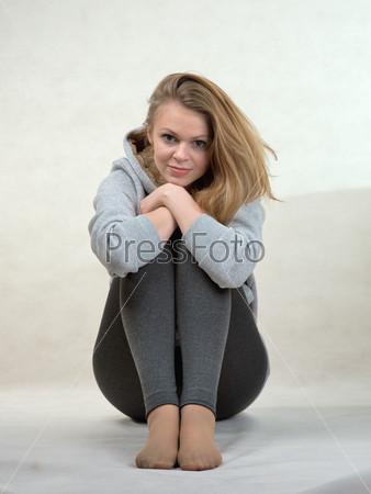 Девушка сидит, сложив руки на коленях