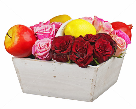 Flower arrangement of red roses and fruits in wooden basket isol