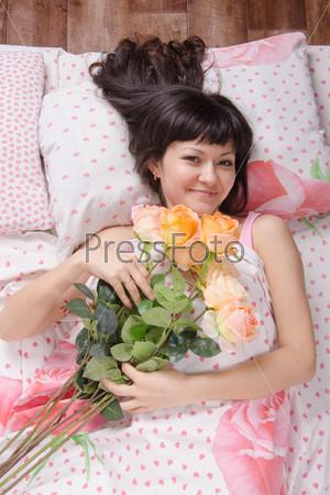 Фото девушки с цветами в постели