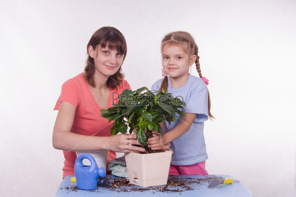 Mom and daughter planting new houseplant in a pot