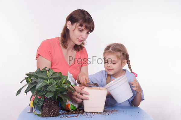 Mother and daughter pour small pot of earth in large