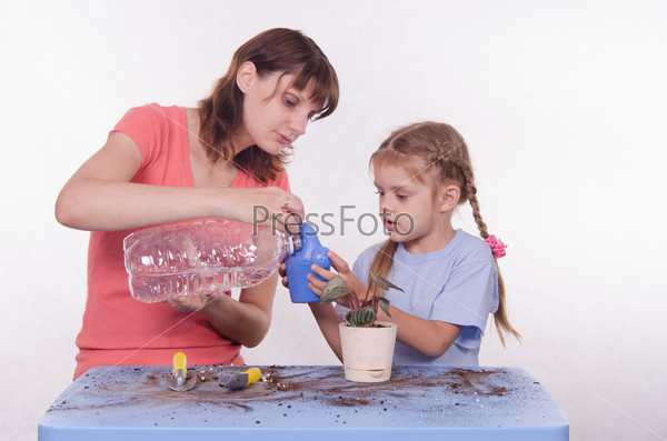 Mom and daughter poured water into a watering can flowers