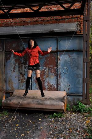 Девушка позирует у разрушенного здания
