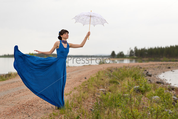 A girl tries to keep a umbrella which pulls out a wind
