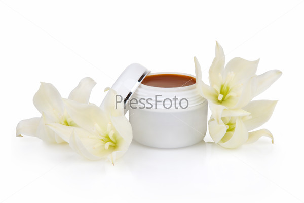 Open jar with the cosmetic cream and flowers isolated on white