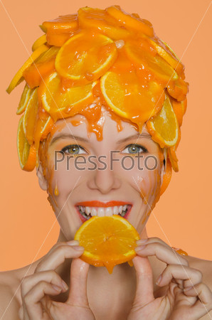 Woman with smile eats  slice of orange