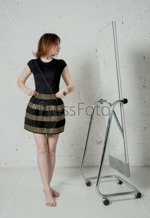 Woman looking in mirror, trying dress