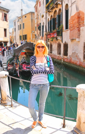 Attractive girl on the waterfront of a narrow canal in Venice, I