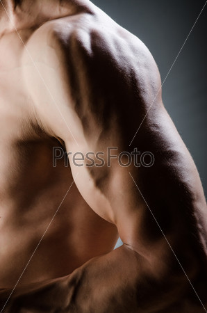 Muscular man posing in dark studio