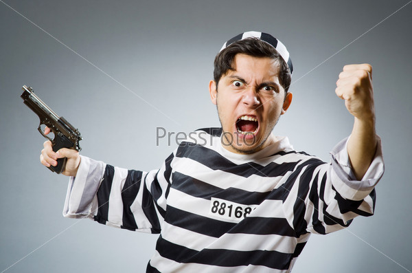 Prisoner with gun against dark background