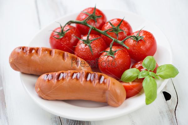 Сосиски-гриль и жареные красные помидоры на ветке