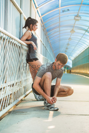 Man and woman tying shoelaces