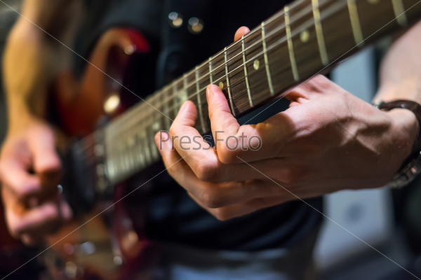musician plays a guitar