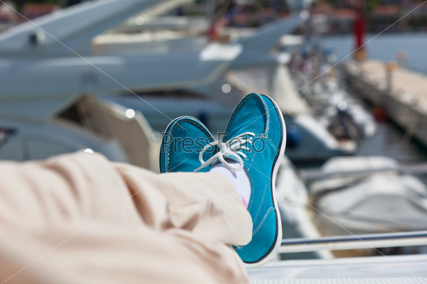 Human legs in pants and bright blue topsiders on yacht