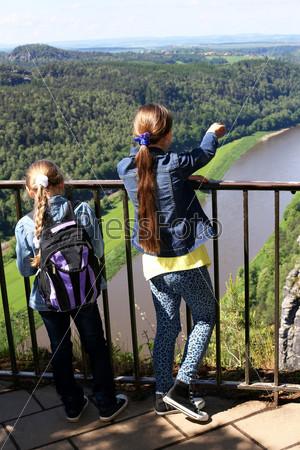 two girls standing on the bridge