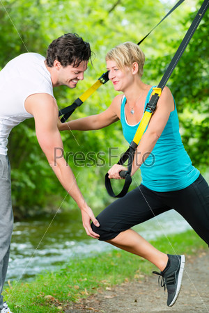 People in park on suspension or sling trainer