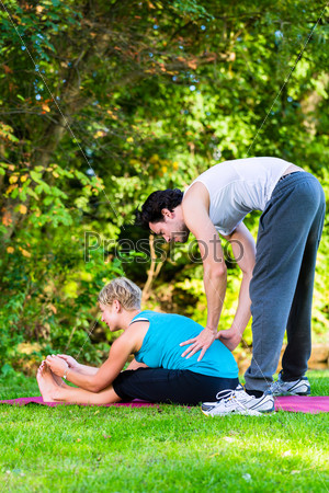 Young woman outdoors doing yoga with trainer