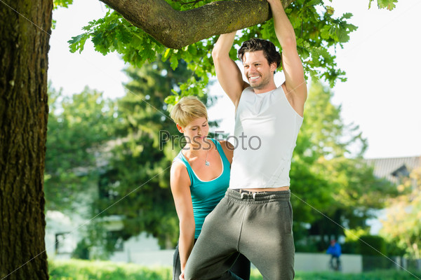People in city park doing chins or pull ups on tree