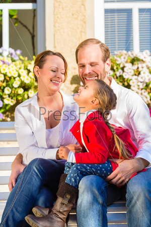 Family on garden bench in front of home