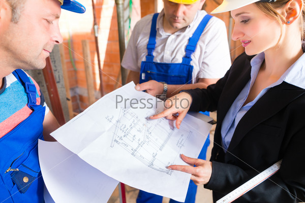 Work Team on construction site controlling floor plan