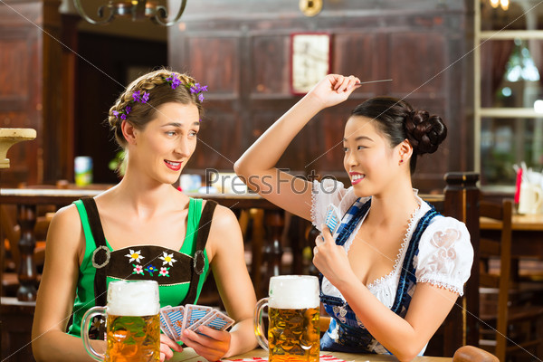friends drinking beer in Bavarian pub playing cards