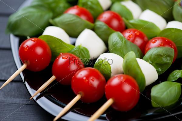 Красные помидоры, сыр моцарелла и зеленый базилик на шампурах