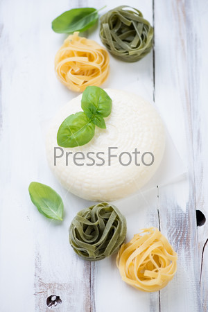 Круглый сыр, листья зеленого базилика и тальятелле