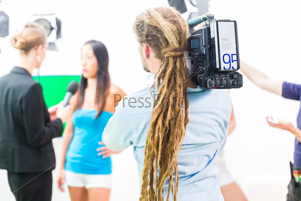Cameraman shooting with camera on film set