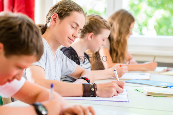 Students writing a test in school concentrating