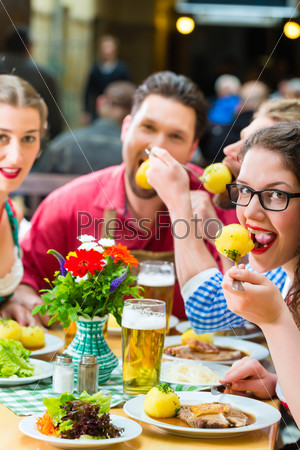 People in bavarian Tracht eating in restaurant or pub