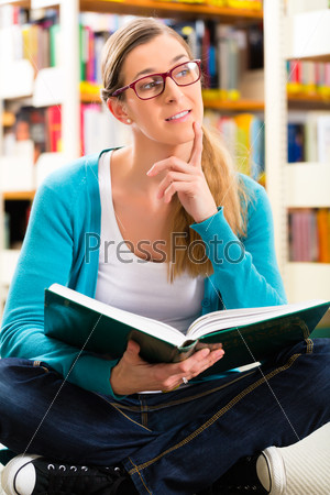 Student with pile of books learning in library