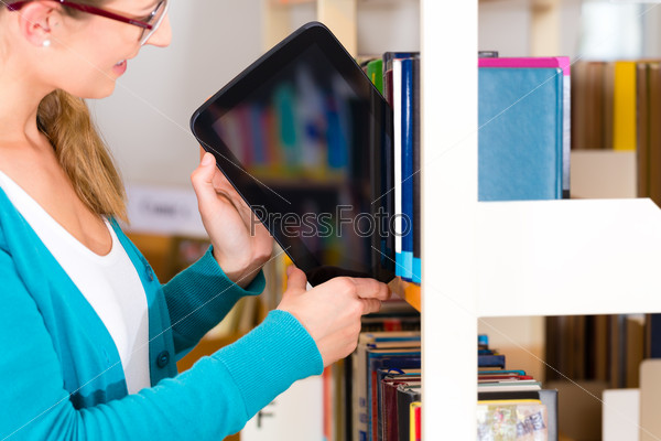 Young Girl in library with e-book or tablet computer