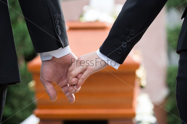 People at funeral consoling each other
