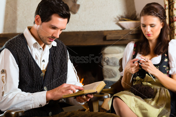 Young couple in mountain hut at fire place