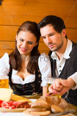 Young couple in a hunters cabin eating
