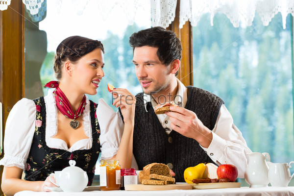 Young couple in a hunter's cabin eating