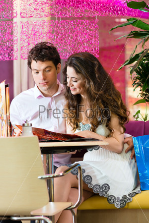 Young couple enjoying coffee after shopping