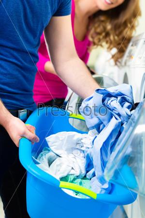 Люди в прачечной с грязным бельем и стиральными машинками на заднем плане