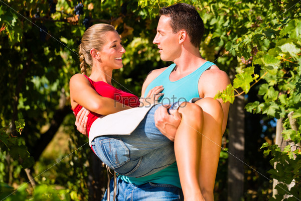 Man carries woman on his arms in vineyard