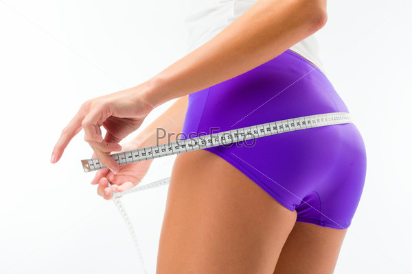 Woman measuring her hip with tape