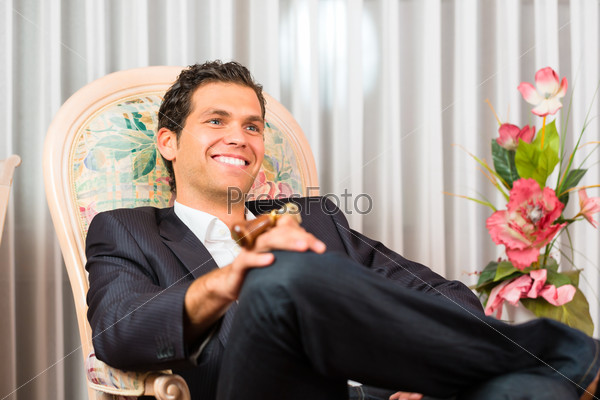 Young man sitting on chair in hotel room