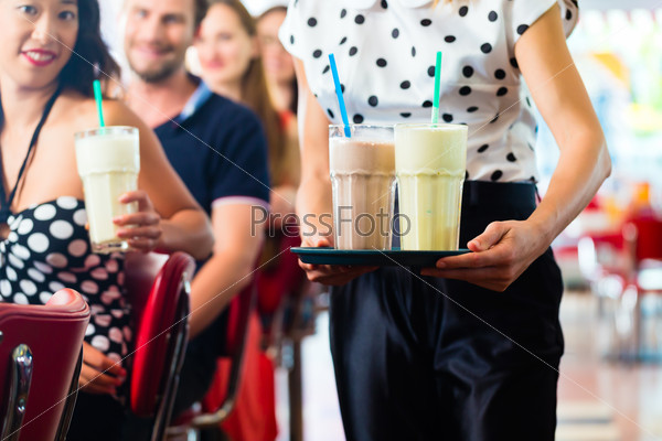 People in American diner or restaurant with milk shakes