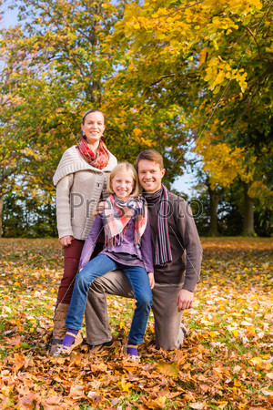 Family in front of colorful trees in autumn or fall