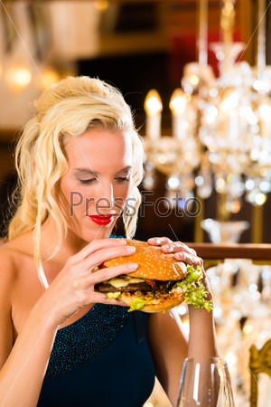 Young woman in fine restaurant, she eats a burger