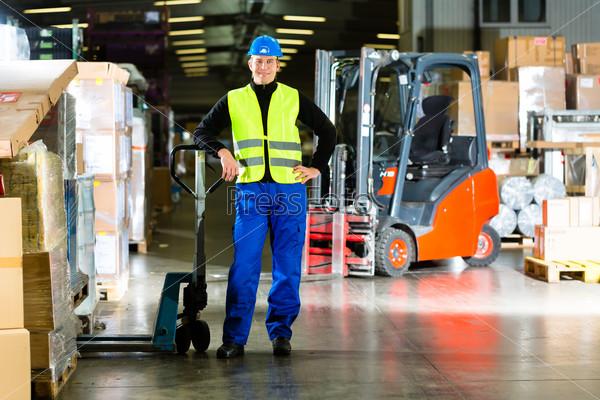 Кладовщик у коробок на складе транспортно-экспедиционной компании и погрузчиком на заднем фоне
