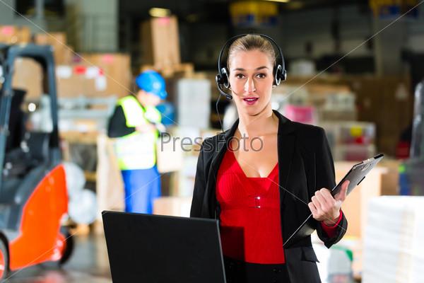 Женщина-руководитель с гарнитурой на складе транспортно-экспедиционной компании