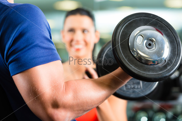Personal Trainer in gym and dumbbell training